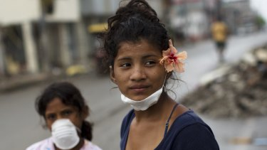 Yesica Zambrano, 15, wearing a flower she found in an earthquake-destroyed home.