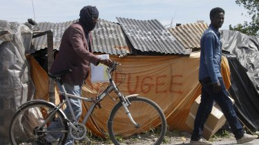 """Migrants walk past a shelter at a makeshift camp known as the """"jungle"""" in Calais, northern France."""