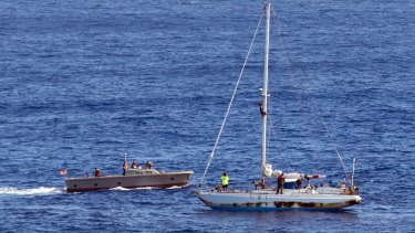 Sailors approach the stricken sailboat with two Honolulu women and their dogs aboard.