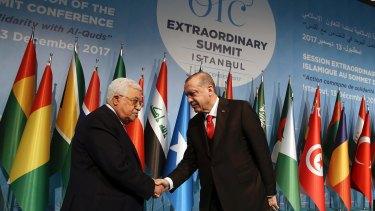 Turkish President Recep Tayyip Erdogan, right, shakes hands with Palestinian President Mahmoud Abbas.