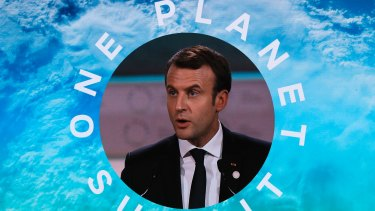 French President Emmanuel Macron is pictured on a screen as he delivers a speech at the One Planet Summit.