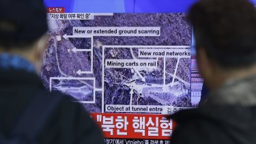 People watch a TV screen showing reports about an 'earthquake' near the test site.