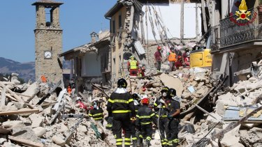 Rescuers work amid collapsed buildings in Amatrice.