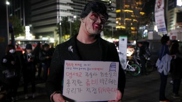 "A protester in Seoul sporting a placard that reads: ""Why do you need Halloween fest? We can see all the horror in our lives."""