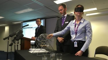 Australian Electoral Commission officials conduct the draw for the Queensland Senate ballot paper.
