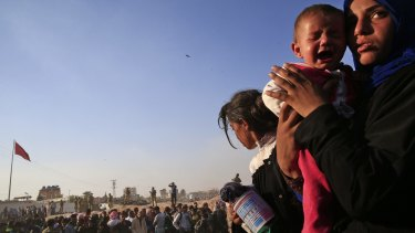 A Syrian refugee holds her baby after crossing into Turkey from Syria in Akcakale.