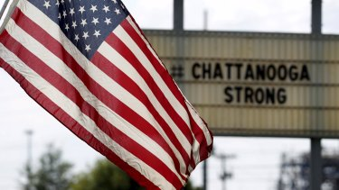 An American flag flies alongside a sign in honour of the four Marines shot and killed in Chattanooga, Tennessee in July.