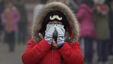 Wearing a mask to avoid breathing air pollution outside the Forbidden City on Tuesday.