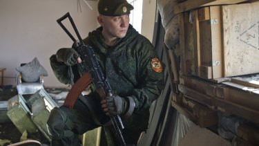 A rebel soldier looks in the direction of Ukrainian forces on the outskirts of Donetsk.