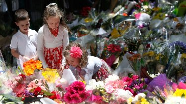 Three children leave a tribute to the victims of the siege in Martin Place.