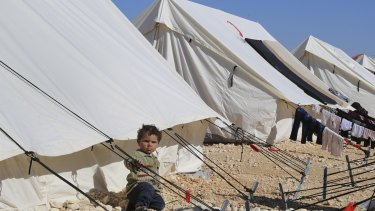 A child plays around a temporary refugee camp for displaced Syrians in northern Syria.