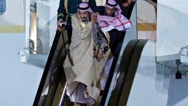 Saudi Arabia's King Salman bin Abdulaziz Al Saud carefully makes his way down the golden escalator.