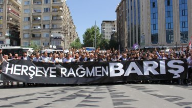 People holding a banner that reads ''Peace despite everything'' march to the site of the attack.