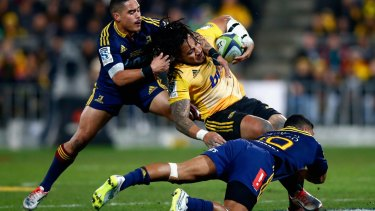 Dumped: Ma'a Nonu of the Hurricanes is tackled by Aaron Smith and Lima Sopoaga.