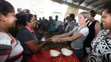 Ms Bishop purchases eggplants in a market in Rakiraki.