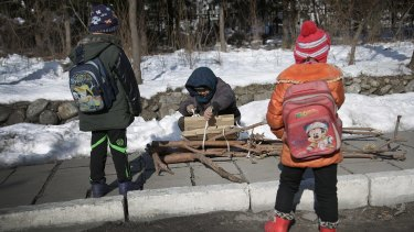 A woman ties wood she collected into a bundle as two children wait in Hyangsan county, North Pyongan, North Korea.