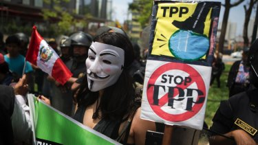 A protester holds signs against the Trans Pacific Partnership during a rally in Lima, Peru, last year.