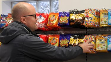 Customer Raymond Arvidsson takes sweets from the display at the shop.