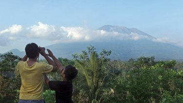 A man observes the Mount Agung with binoculars at a viewing point in Bali, Indonesia.