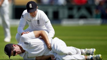 England captain Alastair Cook is consoled by vice-captain Joe Root after being struck in the groin by the ball.