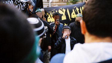 The 16-year-old boy arrested on Wednesday is pictured in 2012, then aged 12, speaking through a megaphone to rioters in Hyde Park.