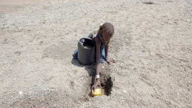A girl digs in a river bed for water in northern Kenya. More than 23 million people in east Africa are facing a critical shortage of water and food, a situation made worse by climate change.