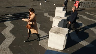 Pedestrians pass bollards in Queensbridge Square on Friday.
