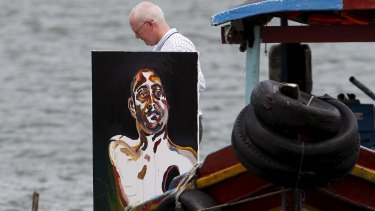 Lawyer Julian McMahon carries Myuran Sukumaran's self portrait of his upper body, with a black hole over his heart.
