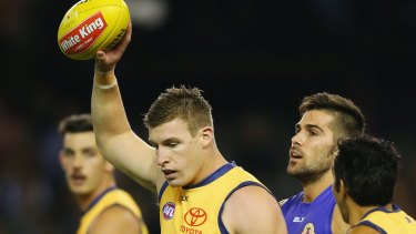 Adelaide's Josh Jenkins, who kicked eight goals, holds the ball up after marking it against Marcus Adams of the Bulldogs.