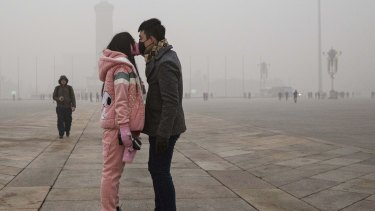 A mask-wearing Chinese couple kiss in Tiananmen Square in Beijing on Tuesday.