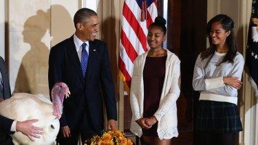 "President Obama ""pardons the turkeys"" with his daughters Sasha and Malia."