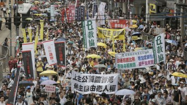 Hundreds of protesters march on a downtown street during an annual pro-democracy protest in Hong Kong in July 2016.