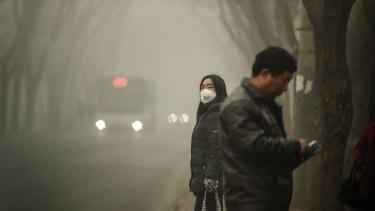 A woman wears a face mask next to traffic shrouded in heavy smog on Tuesday.