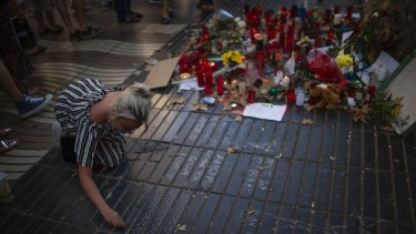 A woman writes a message on the ground at a tribute to those killed and wounded in the Barcelona atrocity.
