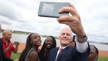Prime Minister Malcolm Turnbull takes a selfie with new Australian citizens Lydia Banda-Mukuka and Chilandu Kalobi Chilaika after the citizenship ceremony.