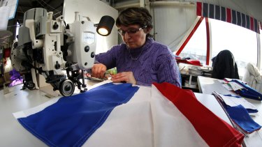Patricia Toillon, 50, works on a French flag at the Doublet factory in Avelin, near Lille, this week.