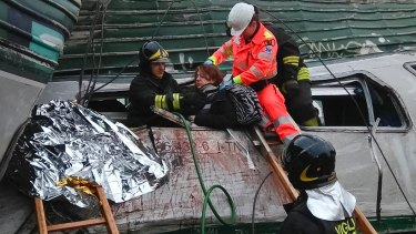 A woman is helped out of the wrecked car of the train.