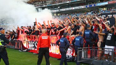 Rogue elements: Wanderers fans hold flares aloft at Etihad Stadium on Saturday.