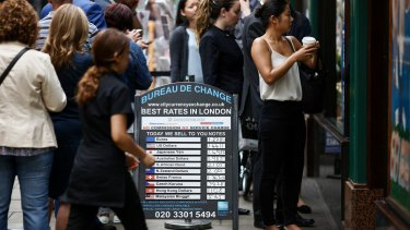 Customers queue outside a foreign currency exchange bureau in London.