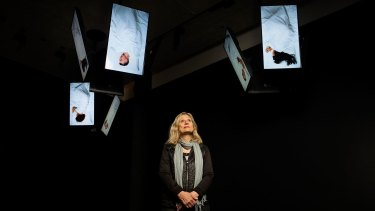 Video installations of artists sleeping hang like bats from the ceiling in artist Julie Rrap's new exhibition.