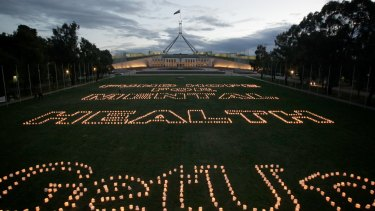 """Thousands of candles are lit on the lawns of Parliament House by GetUp! members spelling the words """"FUND HOPE FOR MENTAL HEALTH""""."""