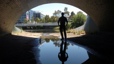 A person stands in one of the main sewerage outlets that flow into the Yarra River.
