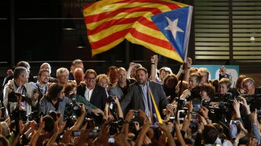 "An ""Estelada"" or pro independence flag flies near the Catalan regional president Artur Mas (left) and Oriol Junqueras, president of the Esquerra Republicana de Catalunya party in Barcelona."