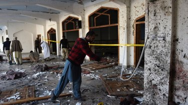 Pakistani security personnel inspect a Shiite mosque after the attack by Taliban militants in Peshawar.