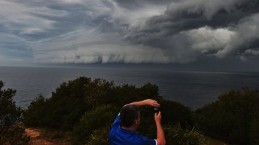 A man photographs a shelf cloud at Mona Vale on Tuesday.