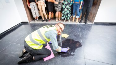 Adam Bandt cleaning the floor of ACCA as part of artist Nat Thomas' installation 'Man Cleaning Up'.