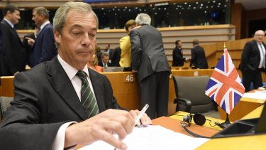 UKIP leader Nigel Farage sits next to a British flag during a special session of European Parliament.