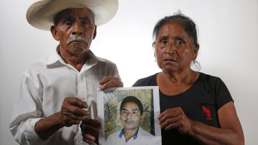 "Matias Fermin Montano, left, and Agustina Ramirez Nemesio, hold up a photo of their missing son, Margarito Fermin Ramirez in Iguala, Mexico. Their son disappeared in 2012, one of the many referred to as the ""other disappeared""."