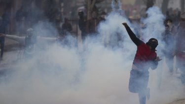 A protester throws back an exploded tear gas shell in Indian controlled Kashmir on Friday. Experts say tight security along the disputed frontier has pushed the focus of militant activity south.