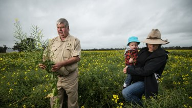 Neil Mattiske with his daughter Joanne and grandson Riley on their flood affected farm near Forbes